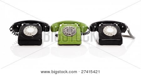 Green phone in the midle of two black phones, isolated on white background