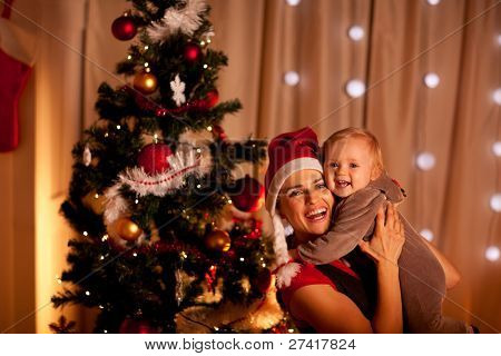 Portrait Of Smiling Young Mother With Beautiful Baby  Near Christmas Tree