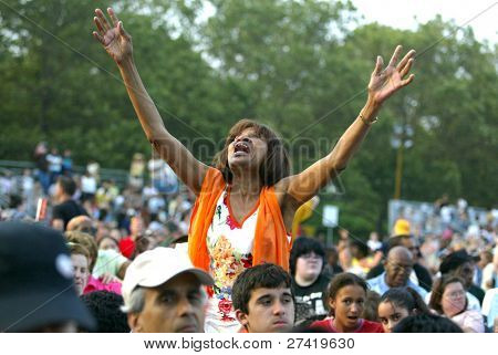 NEW YORK - JUNE 25: An unidentified woman gestures as she prays on the second night of the Billy Graham Crusade at Flushing Meadows Corona Park on June 25, 2005 in Flushing, New York.