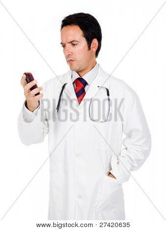 Young doctor reading a message on the phone and looking worried