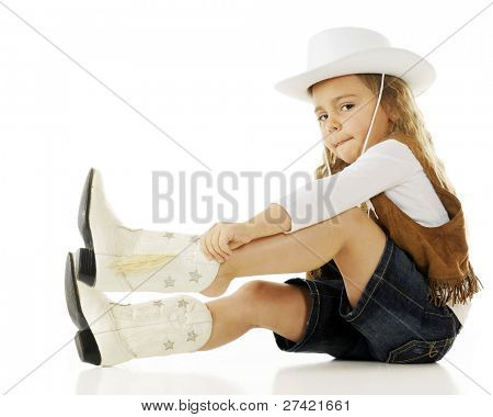 A young cowgirl putting on her boots.  On a white background.