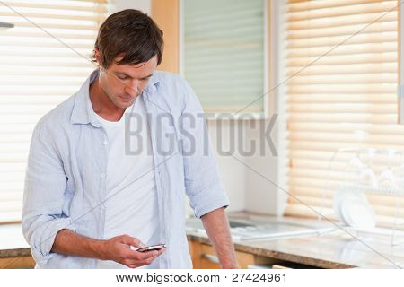 Man using a mobile phone in his kitchen