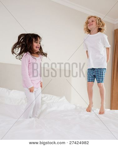 Portrait of children jumping on a bed