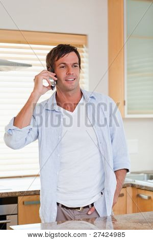 Portrait of a happy man making a phone call in his kitchen