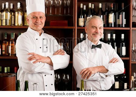 At the bar - happy barman and chef standing cross arms