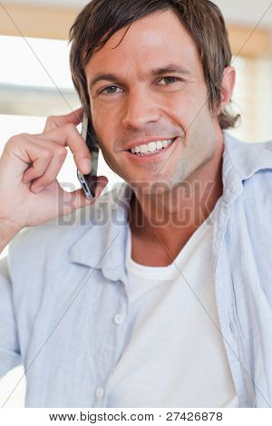 Portrait of an attractive man making a phone call in a kitchen