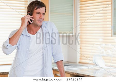 Man making a phone call in his kitchen