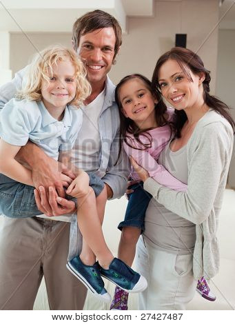 Portrait of a family posing together in a living room