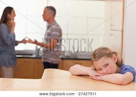 Sad girl hearing her parents fitting in a kitchen