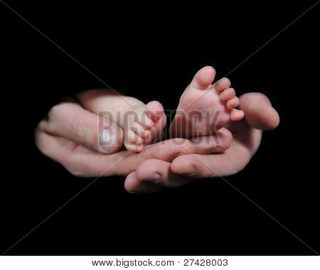 Mans Hands Holding Tiny Baby's Feet, Isolated On Black