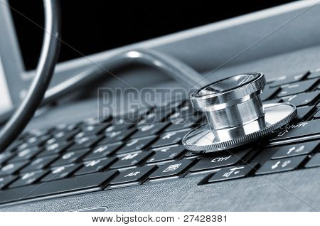 stethoscope on the laptop keyboard, close-up view, blue toned