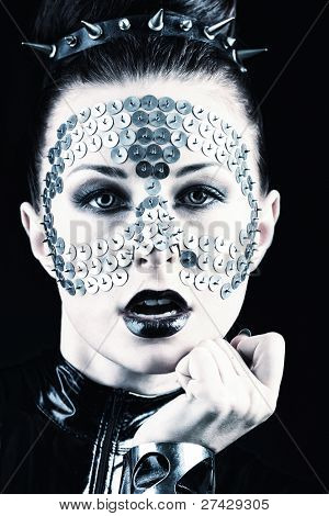 Conceptual shot of a woman in black glossy overall and metal buttons on her face.