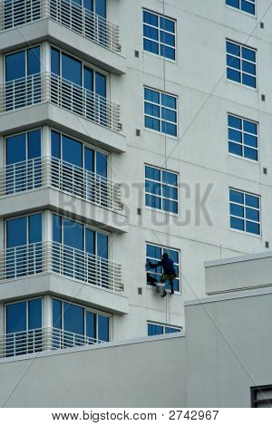 Window Cleaner Cleaning Outside Windows Of A Hotel