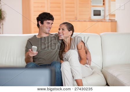 Laughing young couple watching funny movie together