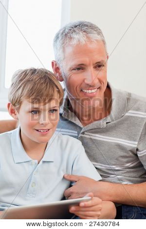 Portrait of a smiling father and his son using a tablet computer in a living room
