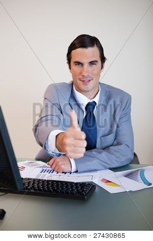 Sitting businessman approves with thumb up