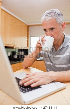 Portrait of a man using a laptop while drinking coffee in a kitchen