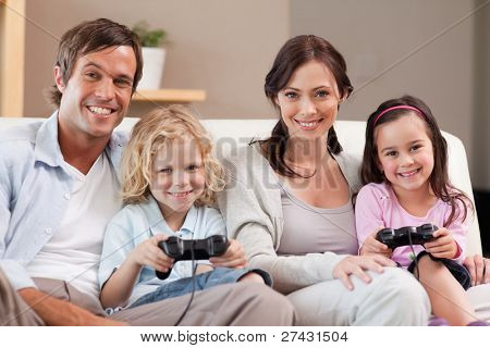 Smiling family playing video games together in a living room