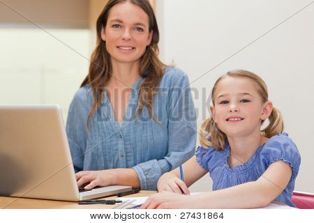 Girl doing her homework while her mother is using notebook in a kitchen