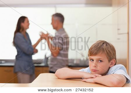 Sad boy hearing his parents having am argument in a kitchen