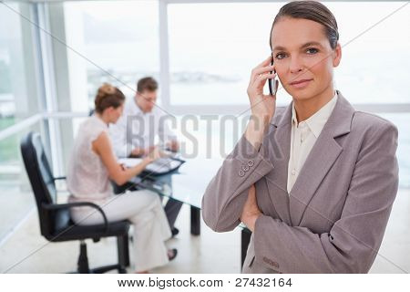 Standing lawyer with cellphone and sitting clients behind her