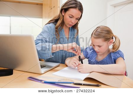 Woman helping her daughter doing her homework in a kitchen