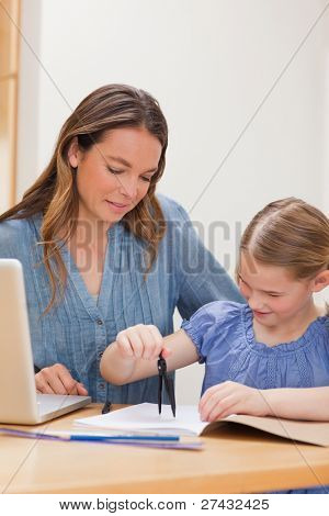 Portrait of a woman helping her daughter doing her homework in a kitchen