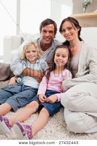Portrait of a family relaxing in their living room while looking at the camera
