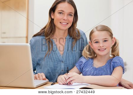 Beautiful woman helping her daughter doing her homework in a kitchen