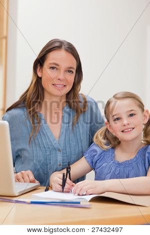 Portrait of a beautiful woman helping her daughter doing her homework in a kitchen