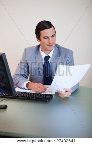Businessman having a look at a contract in his hand