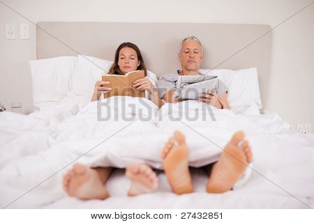 Man reading the news while his wife is reading a book in their bedroom