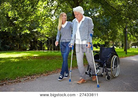 Nurse helping elderly woman with her physiotherapy outdoors