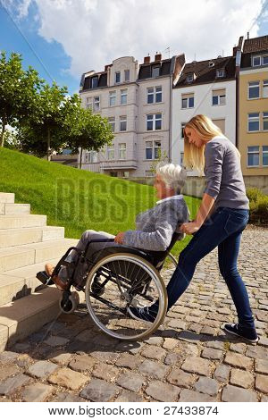 Young woman helping an elderly woman in wheelchair
