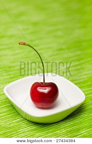 Single red cherry in a white bowl