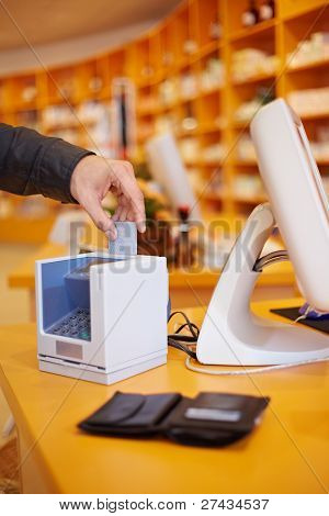 Hand putting credit card in card reader in a pharmacy