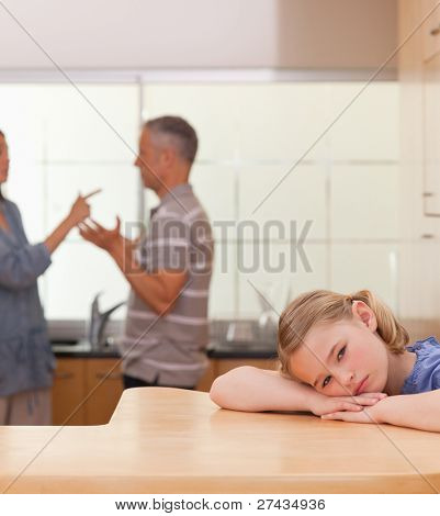 Portrait of a sad girl listening her parents arguing in a kitchen