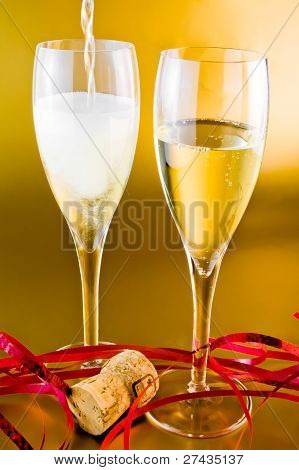 A Pair Of Champagne Flutes With Decoration On Golden Background