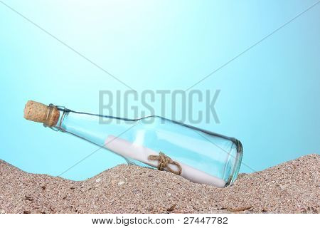 Glass bottle with note inside on sand on blue background