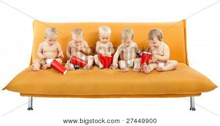 Group Of Children Sitting On Sofa And Eating Popcorn. Isolated White