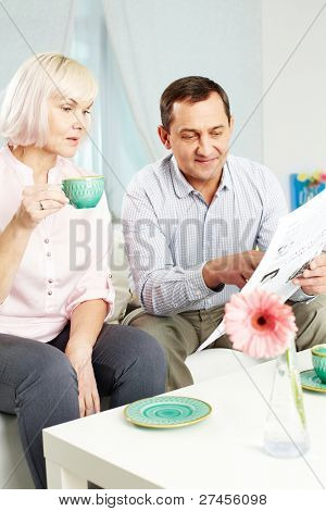 Portrait of mature man and his wife reading newspaper in the morning at home