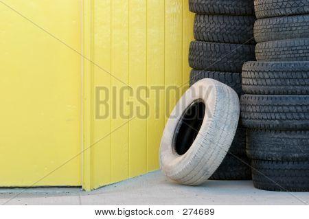 Pila de neumáticos contra la pared amarilla