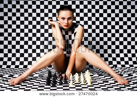 Girl with body-art thinking about progress in chess