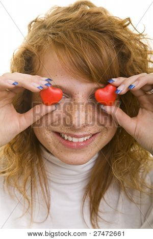Young redheaded woman holding red heart shaped candy in front of her eyes