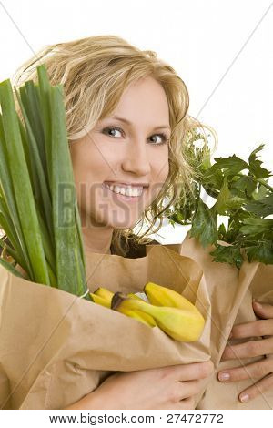 Smiling blond woman carrying fruits and vegetables