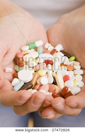 Many colorful pills a two hands