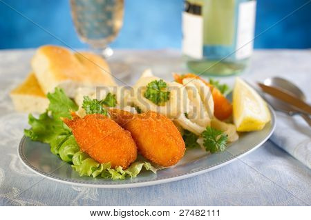 fork with fried crab claws squid ring and salad