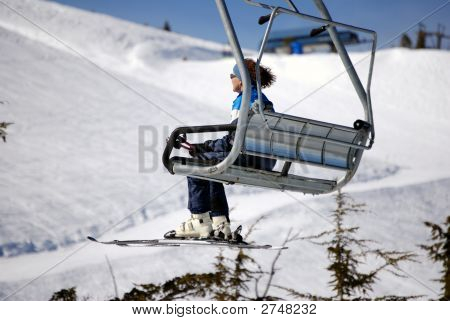 Woman In Blue Riding A Ski Lift Set Against A Snowy Mountain.