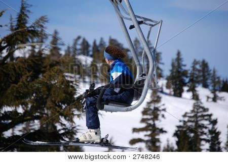 Woman Skier Riding A Ski Lift Against A Snowy Mountain