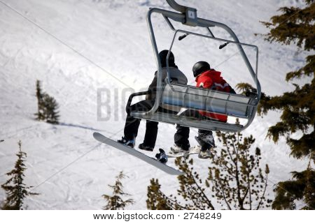 Snowboarders Riding A Chair Lift